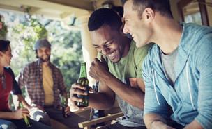 חברים יושבים צוחקים ושותים בירה (צילום: MintImages, Shutterstock)