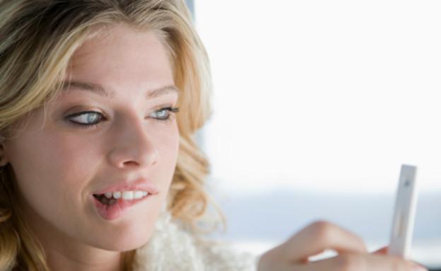 אישה מתבוננת בבדיקת הריון (צילום: אימג'בנק / Thinkstock)