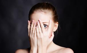 אישה מפחדת מציצה דרך היד (צילום: Ipatov, Shutterstock)