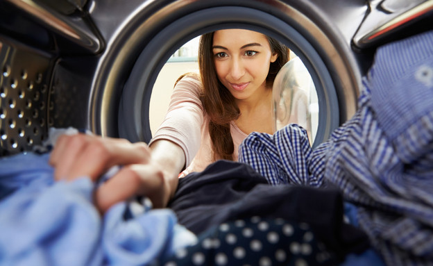 אישה מוציאה בגדים ממייבש כביסה (אילוסטרציה: Monkey Business Images, Shutterstock)