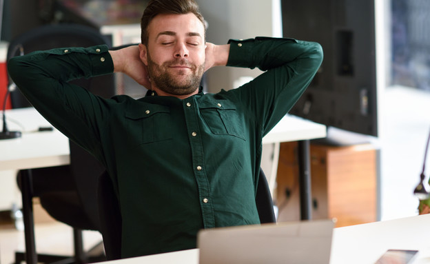 גבר לוקח הפסקה ונח על הכיסא בעבודה (צילום: javi_indy, Shutterstock)