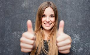 בחורה מחייכת עם אגודלים מורמים (צילום: ShutterStock)