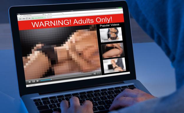 גבר צופה בסרט פורנו על מחשב נייד (צילום: ShutterStock)