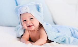 תינוק עטוף בבד כחול (צילום: FamVeld, Shutterstock)