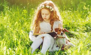 ילדה קוראת ספר עם כלב (צילום: Yuliya Evstratenko, Shutterstock)