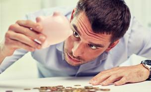 גבר מחפש מטבעות בקופת חיסכון (אילוסטרציה: Syda Productions, Shutterstock)