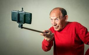 איש מבוגר עם מקל סלפי (צילום: gmstockstudio | ShutterStock)