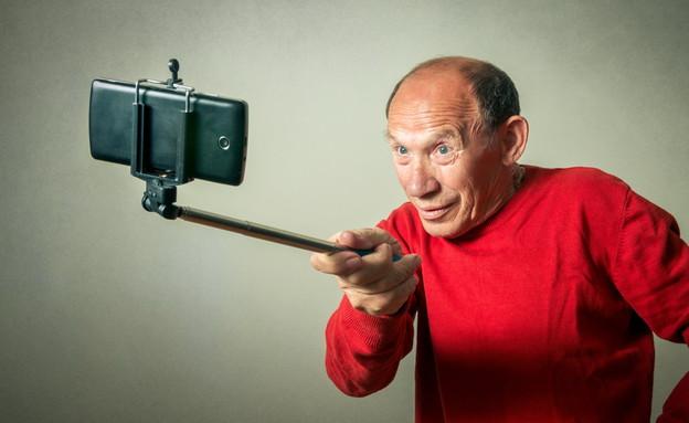 איש מבוגר עם מקל סלפי (צילום: gmstockstudio   ShutterStock)