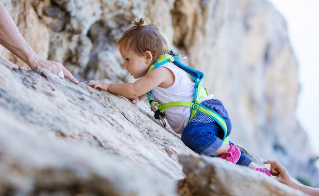 תינוקת עם רתמה מטפסת על צוק (צילום: Photobac, Shutterstock)