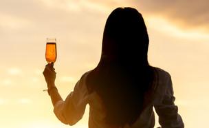 אישה שותה שמפנייה בשקיעה (צילום: Phat1978, Shutterstock)