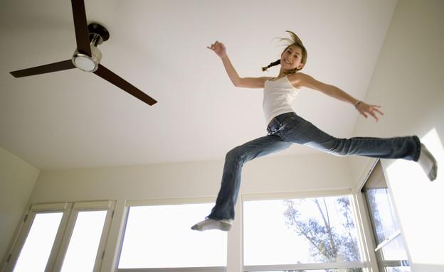 נערה קופצת באוויר ליד מאוורר תקרה (אילוסטרציה: Air Images, Shutterstock)
