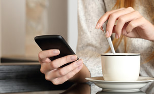 אישה שותה קפה ומסתכלת בטלפון הסלולרי (אילוסטרציה: Antonio Guillem, Shutterstock)
