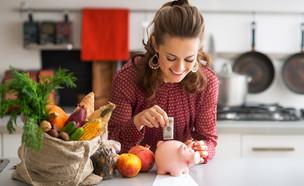 אישה שמחה שמה כסף בקופת חיסכון (צילום: Alliance, Shutterstock)