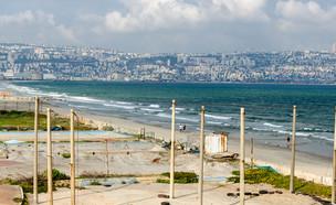חוף ים נטוש בקריית ים על רקע העיר חיפה (צילום: Alex Lerner, Shutterstock)