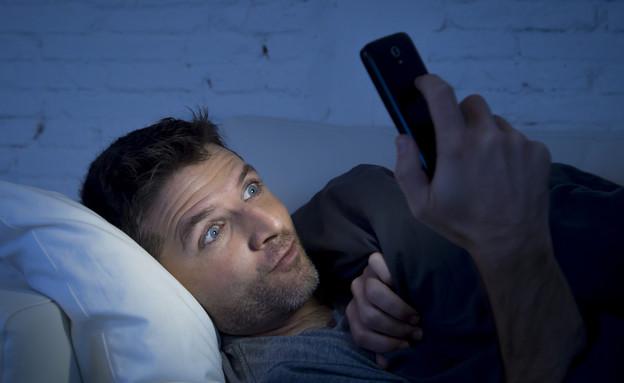 אילוסטרציה: גבר צופה בסמארטפון (צילום: ShutterStock)