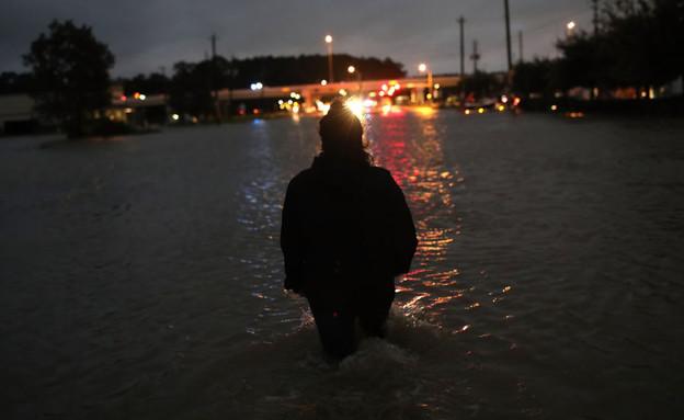 תושב יוסטון הולך ברחוב מוצף (צילום: Win McNamee, GettyImages IL)