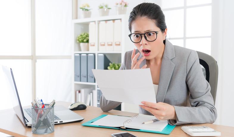 אישה מופתעת קוראת מסמכים (אילוסטרציה: PR Image Factory, Shutterstock)