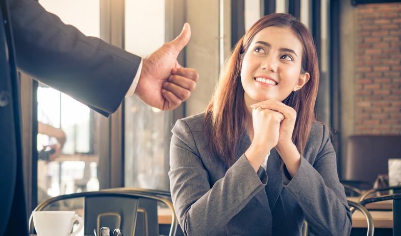 אישה צעירה מחייכת אל הבוס שלה (אילוסטרציה: kateafter | Shutterstock.com )