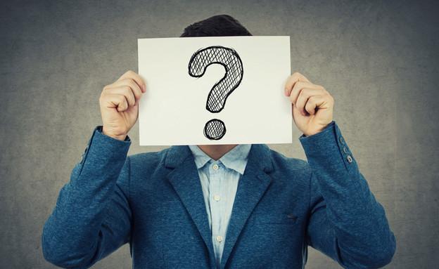 איש מסתיר את פניו בציור של סימן שאלה (צילום: ShutterStock)
