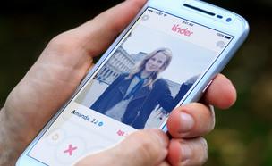 גבר מסתכל על פרופיל של בחורה בטינדר על סמארטפון (צילום: ShutterStock)