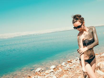 אישה מורחת בוץ בים המלח