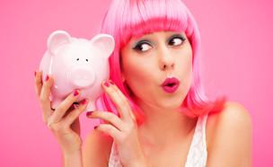 אישה עם שיער ורדו מחזיקה קופת חיסכון (צילום: kateafter | Shutterstock.com )