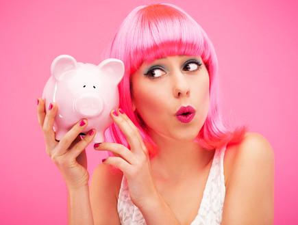 אישה עם שיער ורדו מחזיקה קופת חיסכון