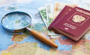 דרכונים עם שטרות כסף על מפת העולם (צילום: By Dafna A.meron)