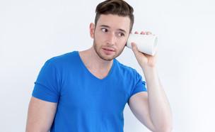 גבר מצותת בעזרת כוס צמודה לאוזן (צילום: יחסי ציבור, ShutterStock)