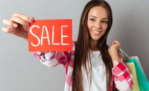 אישה מחזיקה שלט סייל (אילוסטרציה: kateafter | Shutterstock.com )