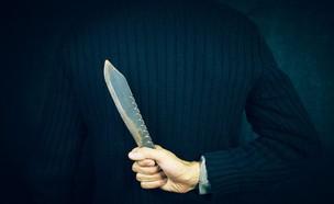 אדם בחליפה מחזיק סכין מאחורי הגב (צילום: Sasun Bughdaryan, ShutterStock)