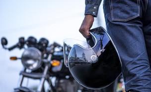 אופנוען מחזיק קסדה (צילום: Virojt Changyencham, ShutterStock)