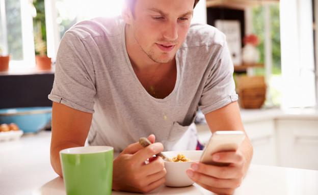 גבר אוכל ארוחת בוקר ומסתכל בטלפון סלולרי