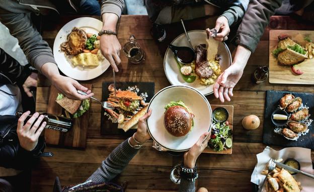 חברים אוכלים במסעדה (צילום: kateafter | Shutterstock.com )