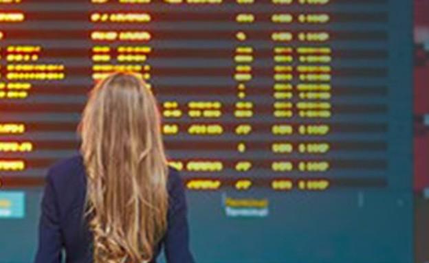 אישה עומדת מול לוח טיסות (צילום: Ekaterina Pokrovsky, Shutterstock)