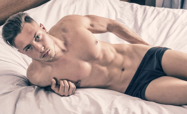 בחור במיטה (צילום: ArtOfPhotos, ShutterStock)