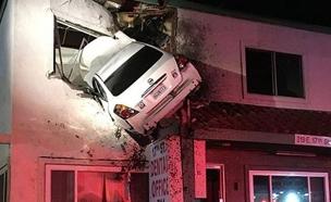 המשטרה מחלצת את  הרכב שתקוע בקומה השנייה. צפו (צילום: AP)