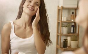 בחורה מורחת קרם פנים (צילום: shutterstock)