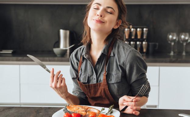 אישה אוכלת דג (צילום: shutterstock)