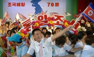 חגיגות על רקע דגל קוריאה המאוחדת (צילום: רויטרס)