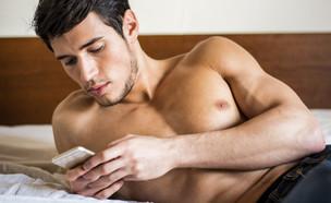 גבר מסמס במיטה (צילום: ArtOfPhotos, ShutterStock)