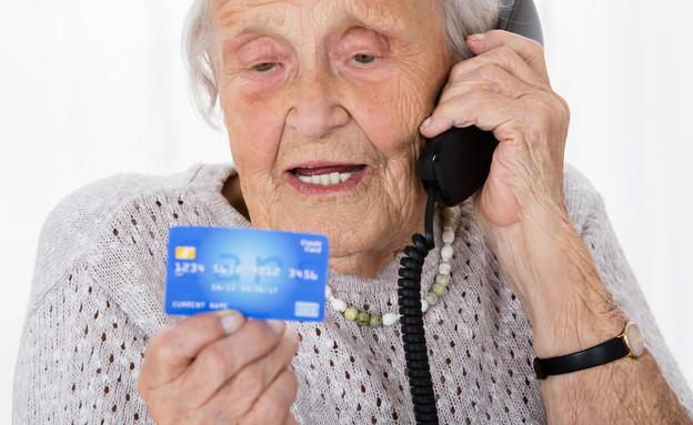 קשישה מדברת בטלפון ומחזיקה כרטיס אשראי (אילוסטרציה: By Dafna A.meron, shutterstock)