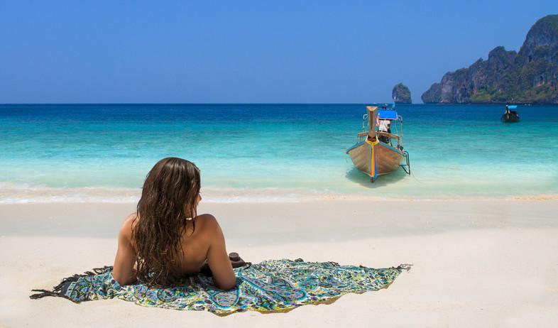 אישה יושבת על חוף בתאילנד (צילום: Netfalls - Remy Musser, Shutterstock)