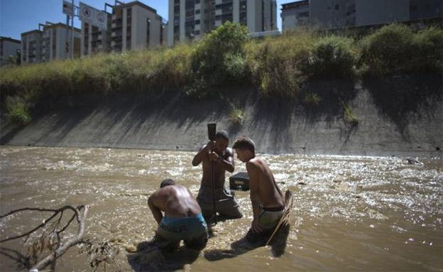 תושבי ונצואלה מחפשים עתיד בנהר המזוהם (צילום: AP)