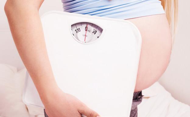 אישה בהריון מחזיקה משקל (אילוסטרציה: By Dafna A.meron, shutterstock)