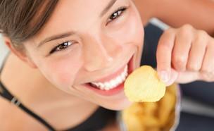 אישה אוכלת חטיף צ'יפס (צילום: shutterstock)