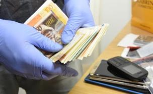 חלק מהכסף שנתפס בבתי החשודים (צילום: דוברות המשטרה)