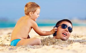 ילד מגיש טלפון סלולרי לאביו הקבור בחול (אילוסטרציה: Olesia Bilkei, shutterstock)