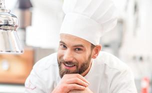 שף במדים עם מנה במטבח (צילום: RossHelen, Shutterstock)