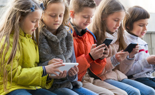 ילדים משחקים בסמארטפון (צילום: Iakov Filimonov, Shutterstock)